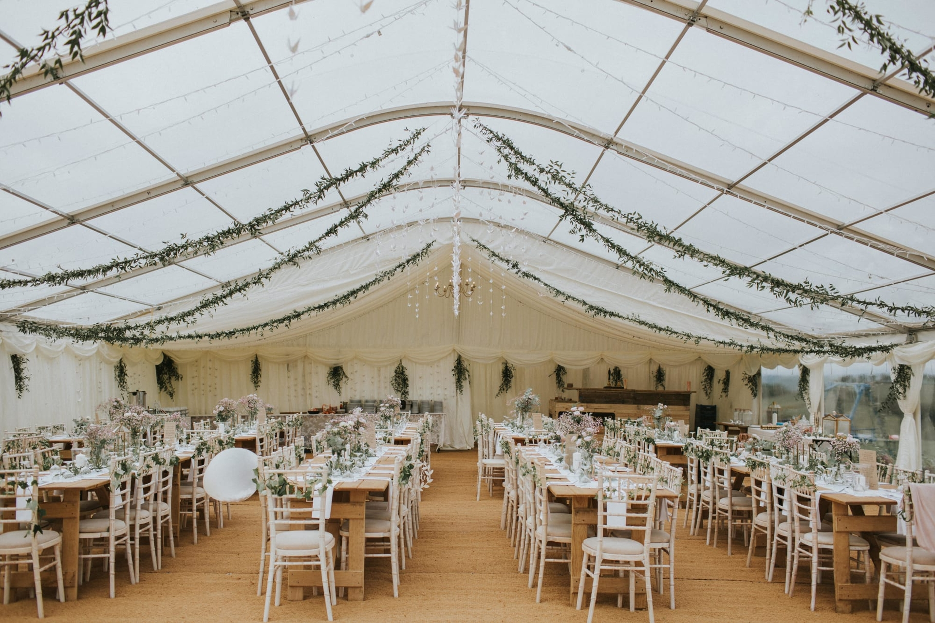 Long rows of tables formally set up in a wedding reception marquee