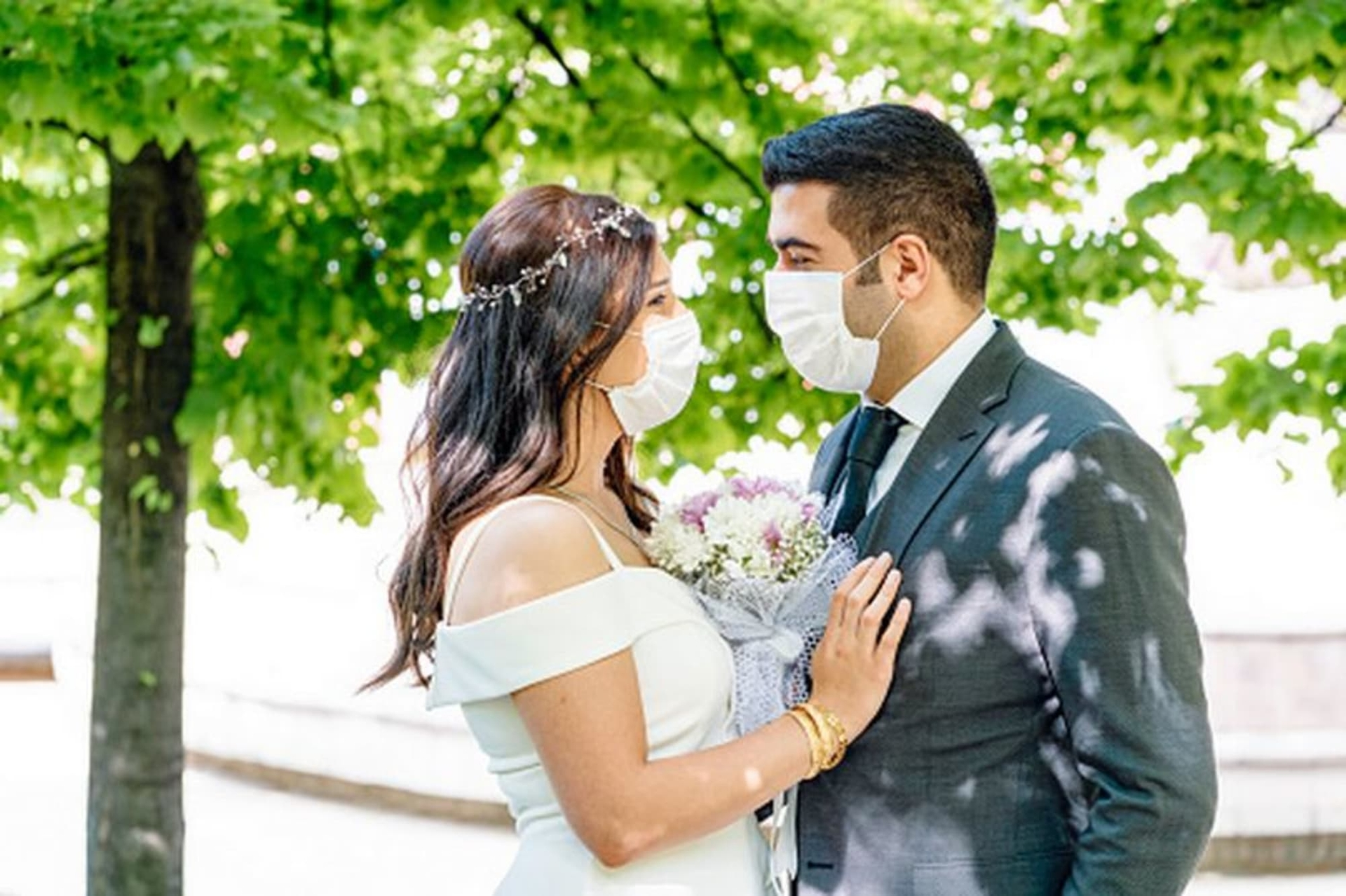 A newly wed couple with face masks stood in front of a tree