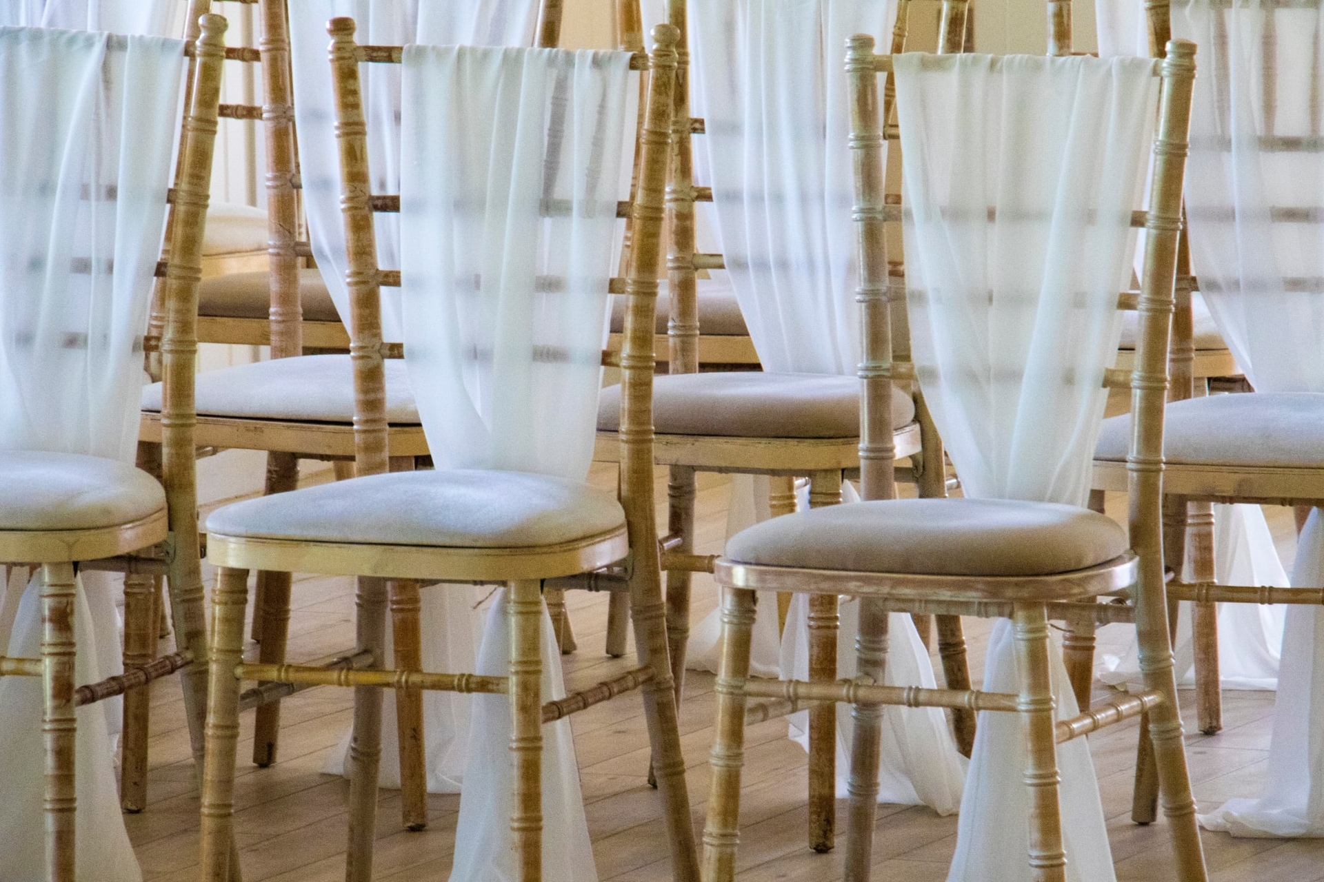 lime-washed chivari chairs in rows set out for a wedding reception