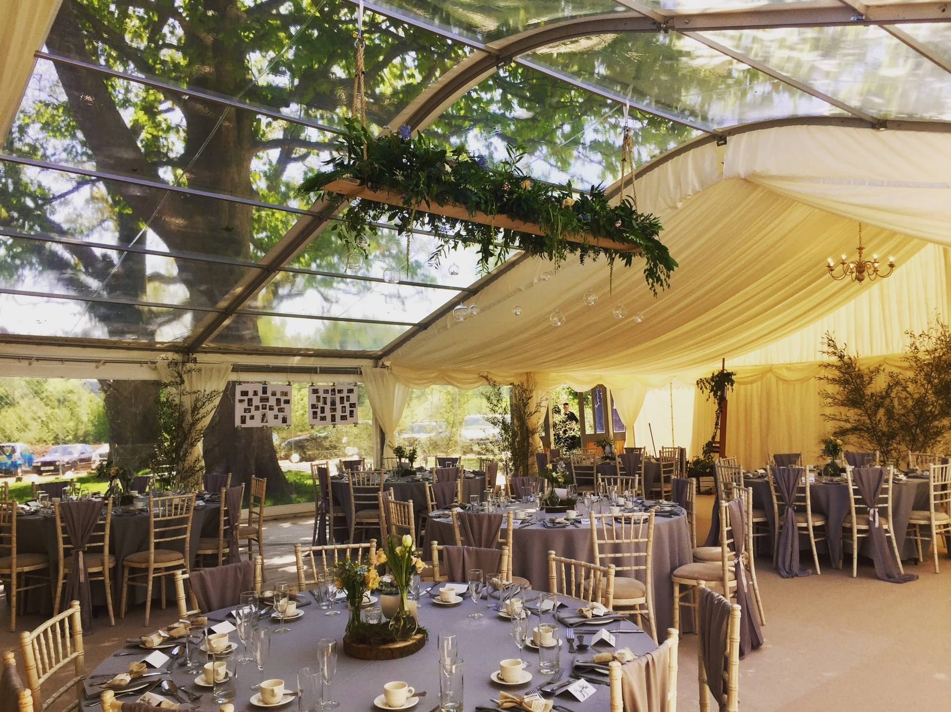 Fomral dining area in a clear roof marquee with ivory linings and round tables